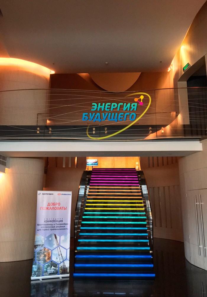 Эскиз: многоцветная подсветка лестницы светодиодной лентой Lightstar LED Strip в цветах конференции логотип конференции